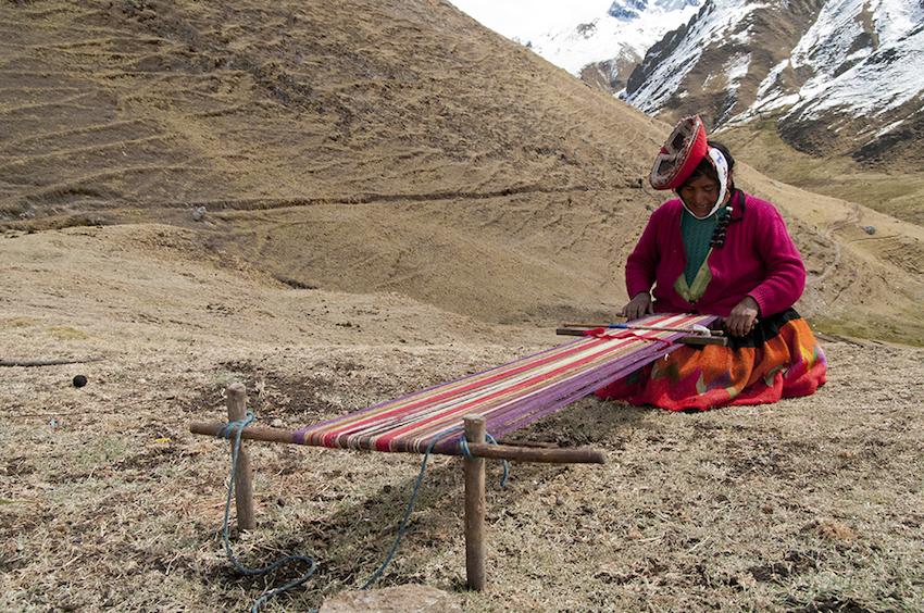 quechuan woman weaving on a loom outside.