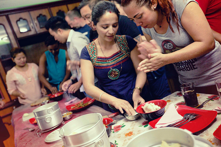 Travellers learn how to make traditional dumplings from the women enrolled in the program.