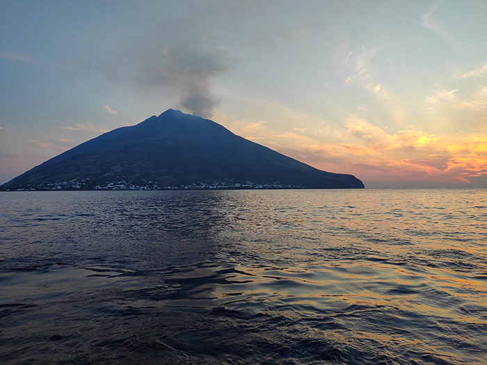 Watch smoke plume from Mount Stromboli as the sun sets on the water