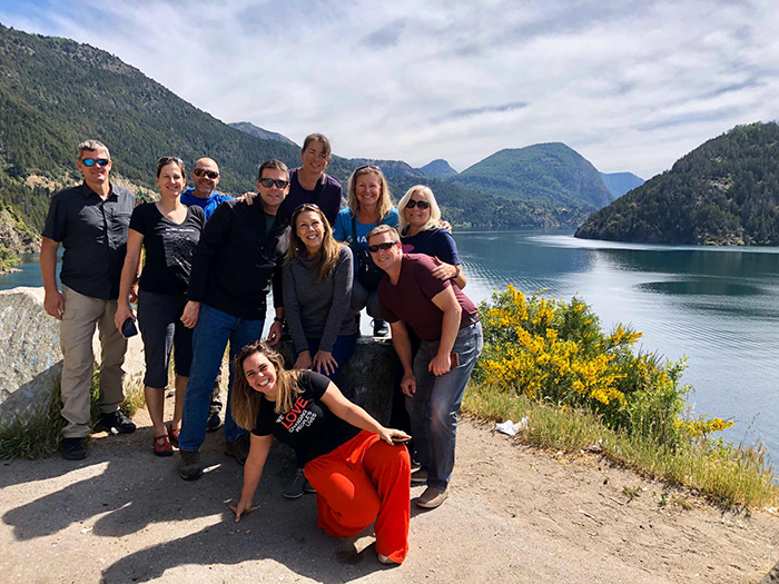 The superfriends including CEO Fernanda are all smiles surrounded by alpine lakes