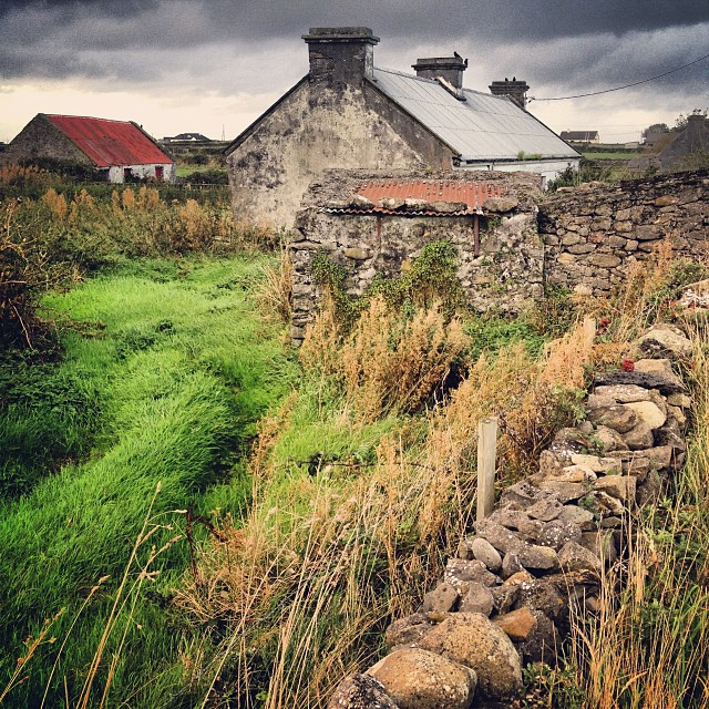 Country back roads of County Sligo, Ireland where the hills are dotted by old Irish farmhouses with rusted roofs and heavy stone walls.