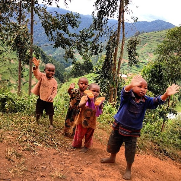 children on the dusty road waving and smiling