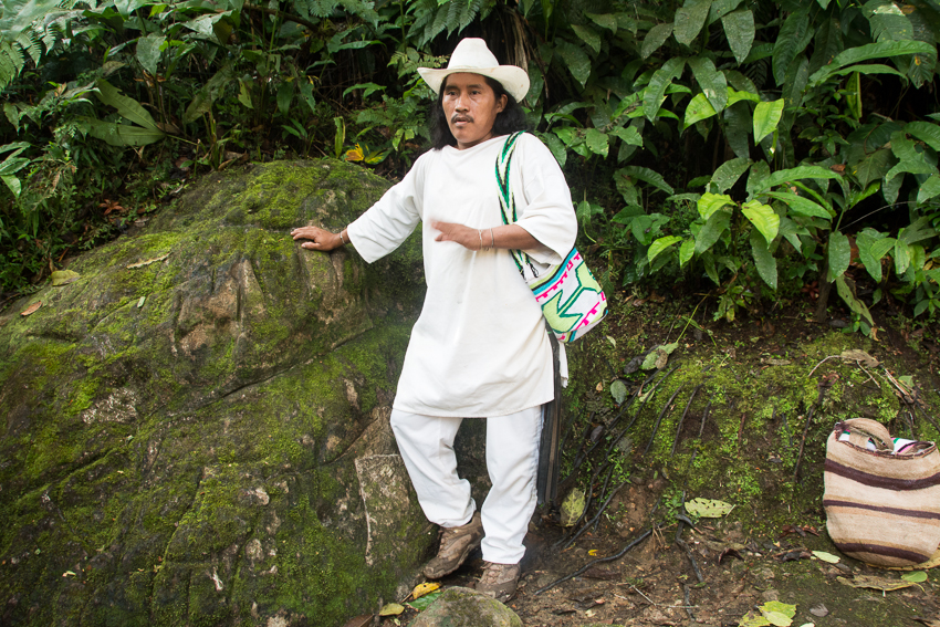 A traditional Wiwa outfit with white cotton clothing, long hair, hat, and woven bags – one for supplies, one for coca leaves.