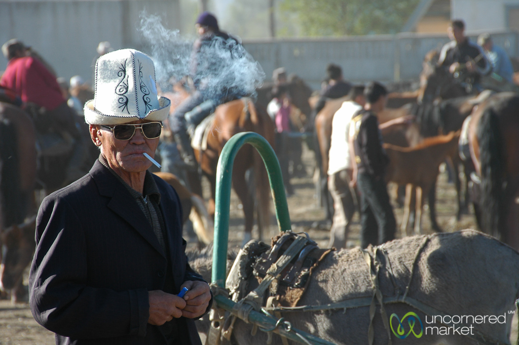 A Kyrgyz man in a traditional hat — kalpak — at the animal market.