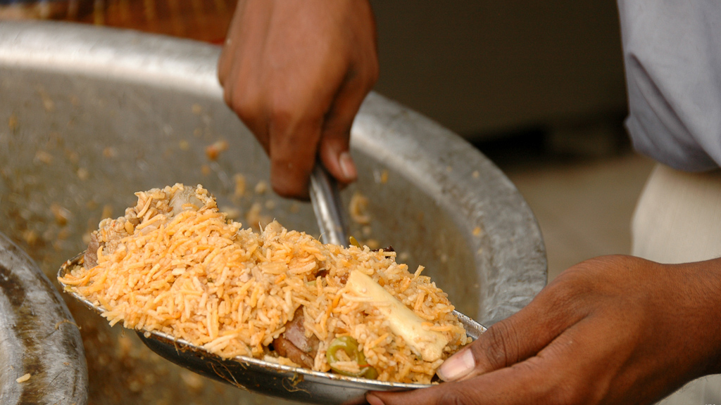 Scooping out a plate of biryani from a pot that's been cooking all day.