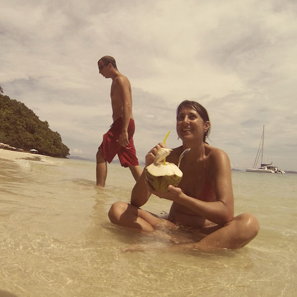 sititng in the water drinking a coconut