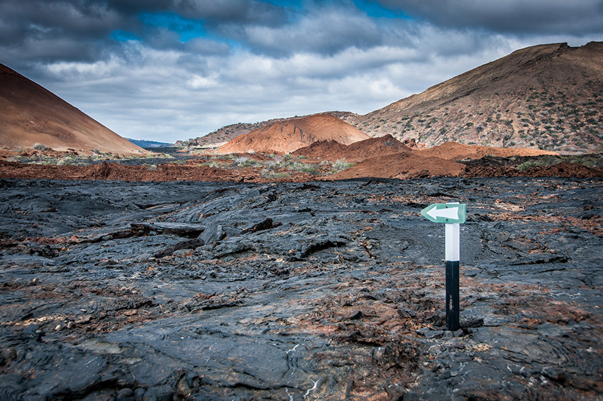A wooden sign marks a path on this rocky landscape in the Galápagos.