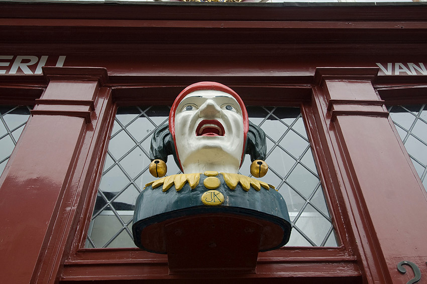 Commercial buildings in the Netherlands traditionally had a carved head or something similar on the storefront sign to let people know what sort of establishment it was. Here is an old bust on the top of a pharmacy in The Hague.