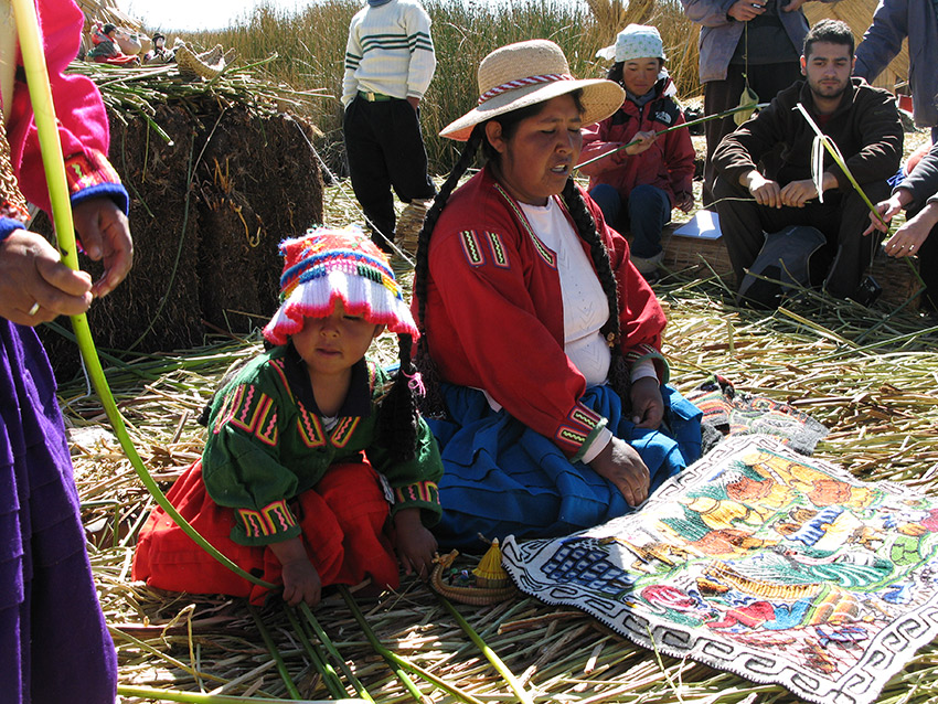 Local Uros using images on a woven blanket to explain their traditions and customs.