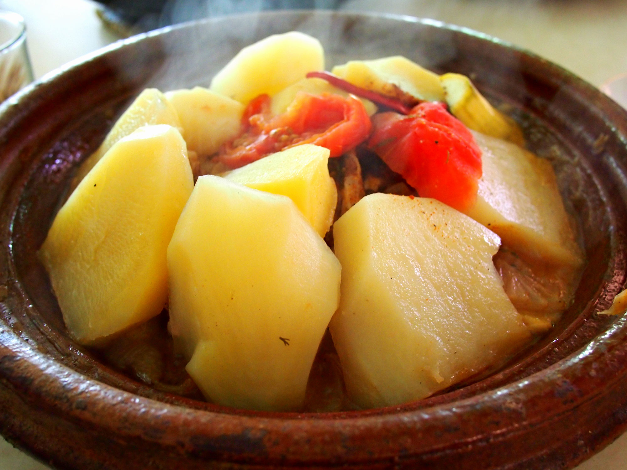Potatoes cover up the meat and vegetables below in this chicken tagine from Morocco.