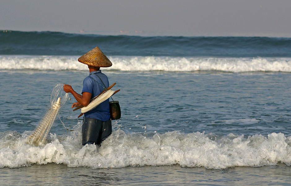 A man fishing traditional style in the waves off the Kai Islands.