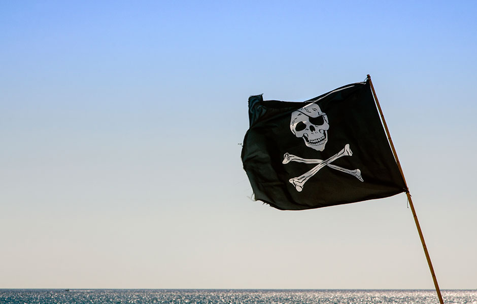 Pirate flag waving with the Caribbean Sea hugging the horizon.