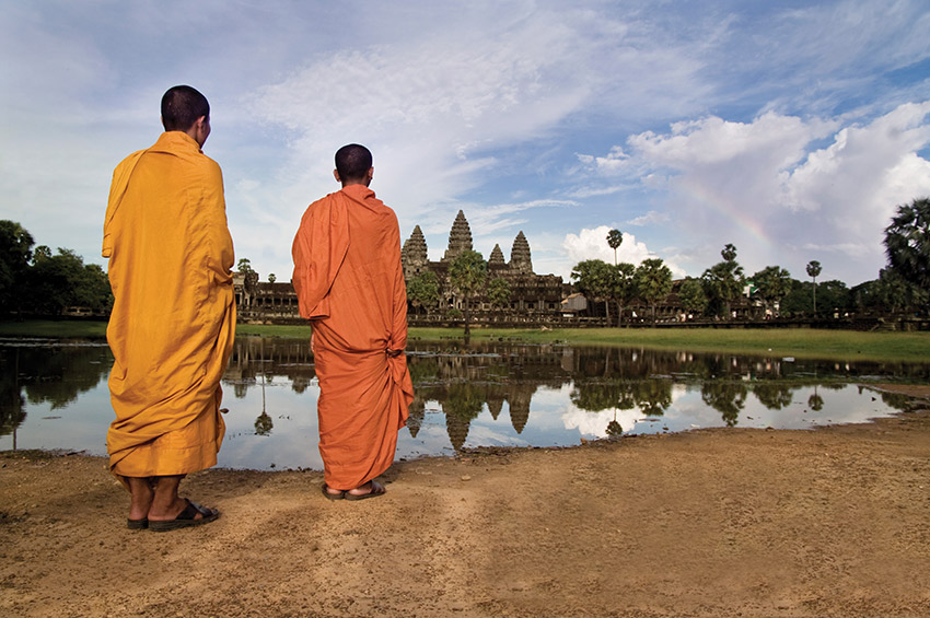 Monks stand watching Angkor Wat.