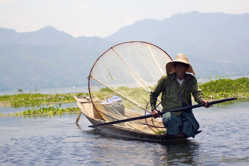 A fisherman with a large conical-shaped fish trap.