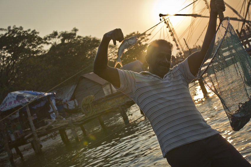 A fisherman holds up his catch in Kochi.