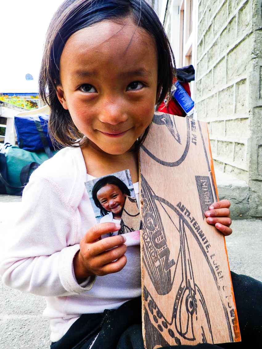 girl in nepal holding a printed copy of her portrait.