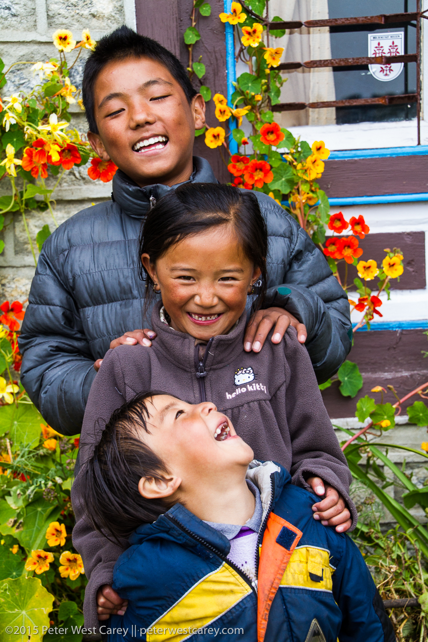 three kids lined up and smiling for the camera in nepal.