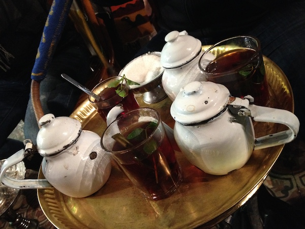 a tray with tea pots and glasses of mint tea
