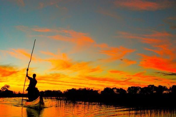 A mokoro canoe cuts through the stillness of twilight in the Okavango Delta, Botswana.