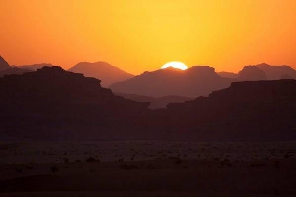 Glowing sky at sundown over the mountains of Wadi Rum, Jordan.
