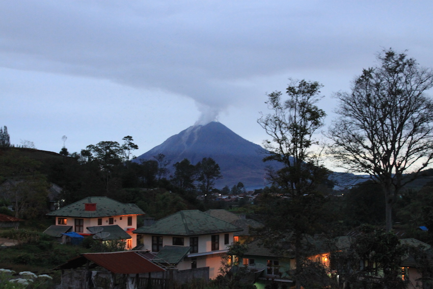 Smoky Sinabung Volcano seen from the charming village of Berastagi.