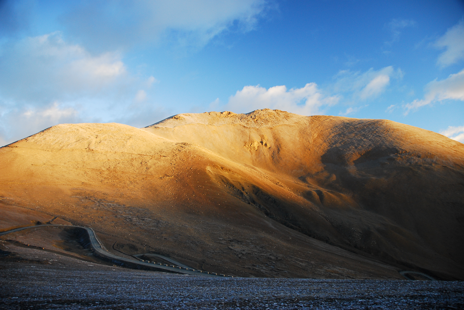 The arid and brown landscape of the Tibetan Plateau sits in stark contrast to the blue skies above it.